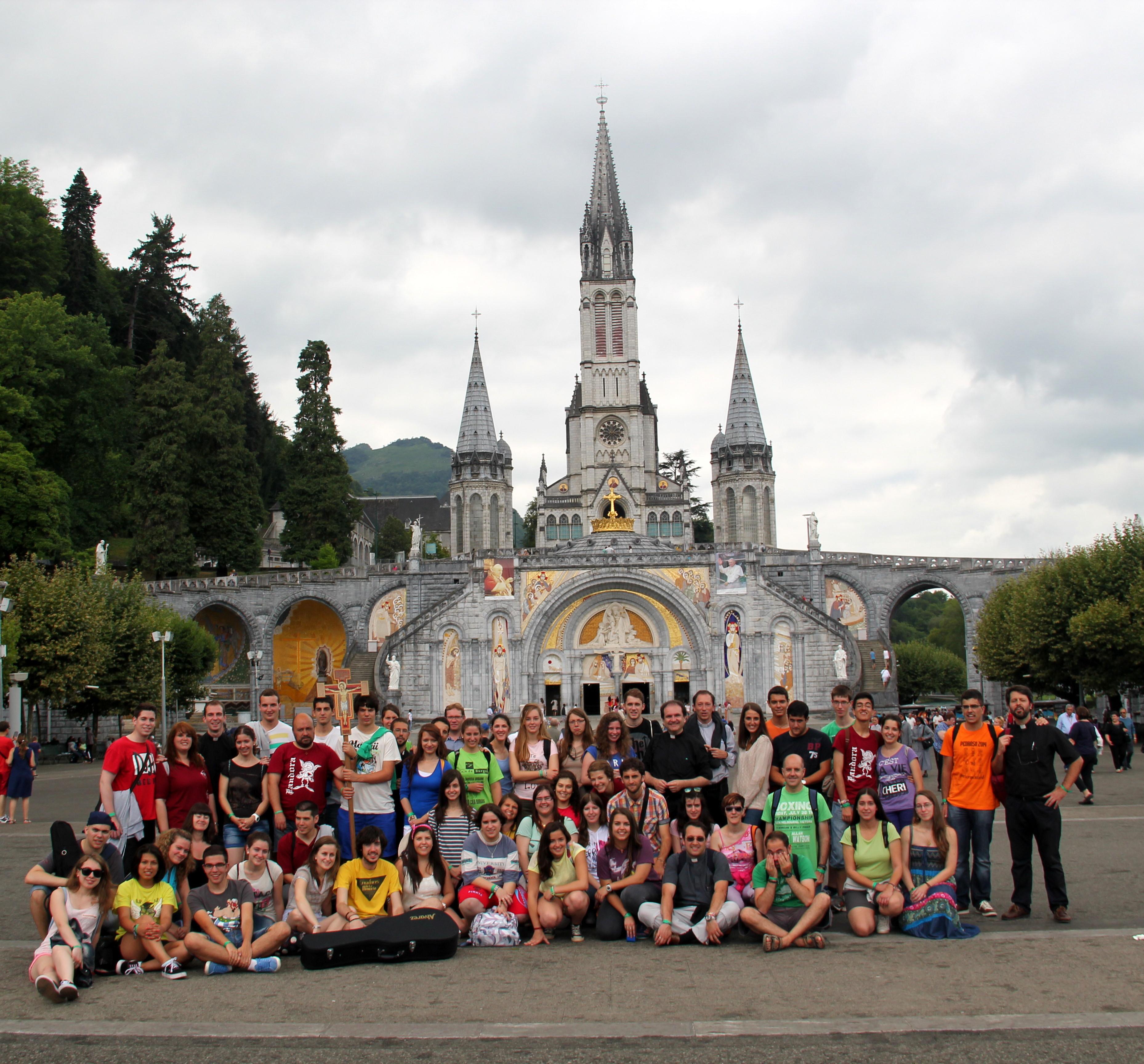 Los jóvenes de la diócesis posan para una foto frente a la basílica de Lourdes.